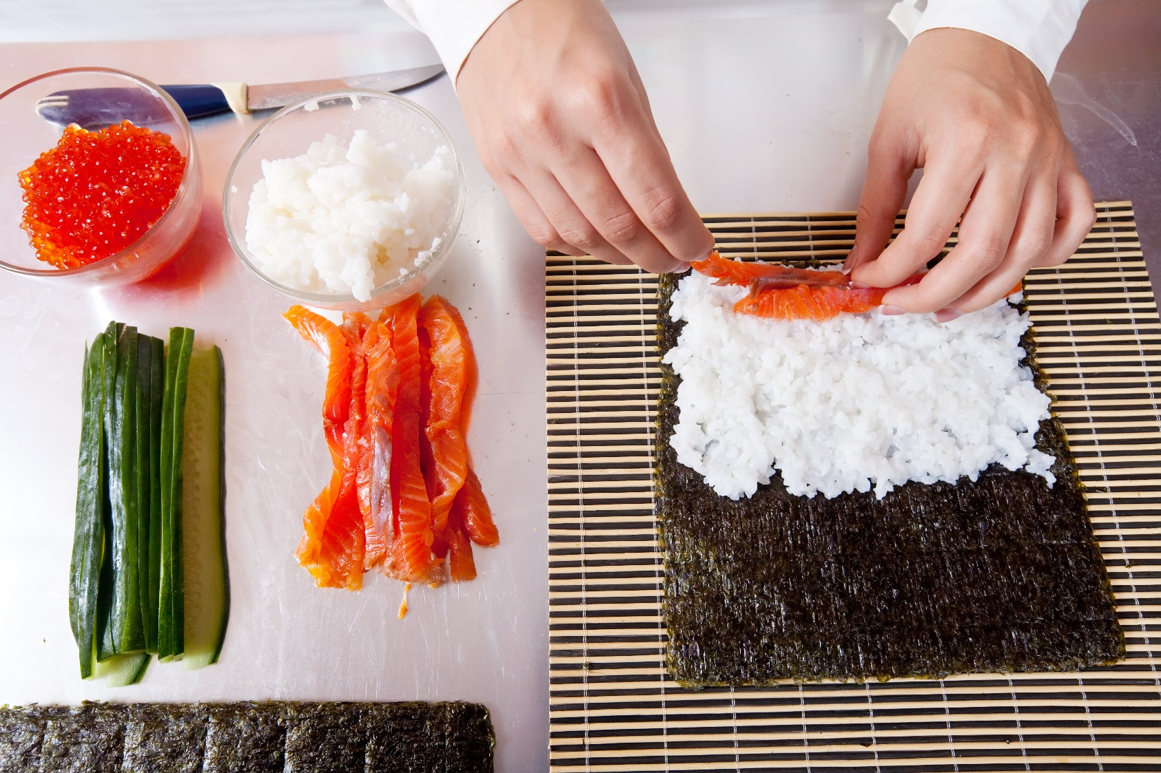 cook making  Japanese sushi rolls