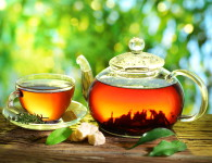 Cup of tea and teapot on a blurred background of nature.